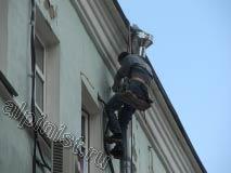 На этой фотографии наш промышленный альпинист крепит ухватом (скобой) водосточную трубу,  сам ухват предварительно был закреплен к стене.