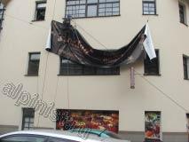 На данном объекте наши промышленные альпинисты проводят монтаж рекламного баннера на стену здания. Верхние края баннера через люверсы мы прикрепили специальным снаряжением и подняли веревками к месту монтажа