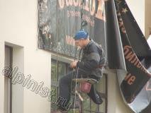 На этой фотографии видно, каким образом крепится баннер к стене здания. Наш промышленный альпинист предварительно прикрутил дюбели с кольцами к стене, а затем через эти кольца и люверсы на баннере продел и натянул репшнур
