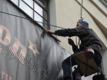 На данной фотографии видно, как наш промышленный альпинист продевает репшнур через люверсы на баннере и пропускает через кольца дюбелей, прикрученные к стене, а затем натягивает этот репшнур для того, чтобы разгладить складки на банере