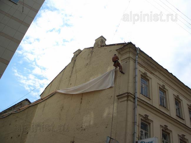 альпинист готовится крепить боковую часть баннера, продевая репшнур через люверсы и кольца дюбелей, прикрученные к стене